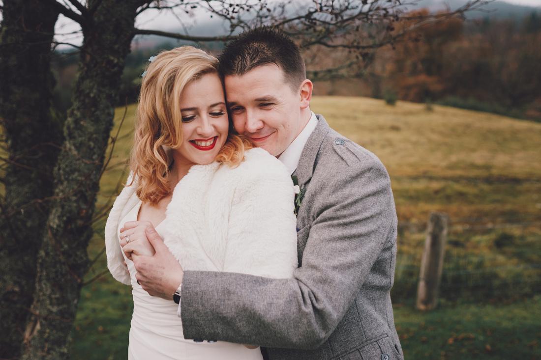 Bride and Groom cuddles Mountains forest Kinlochard Village Hall Wedding Scotland