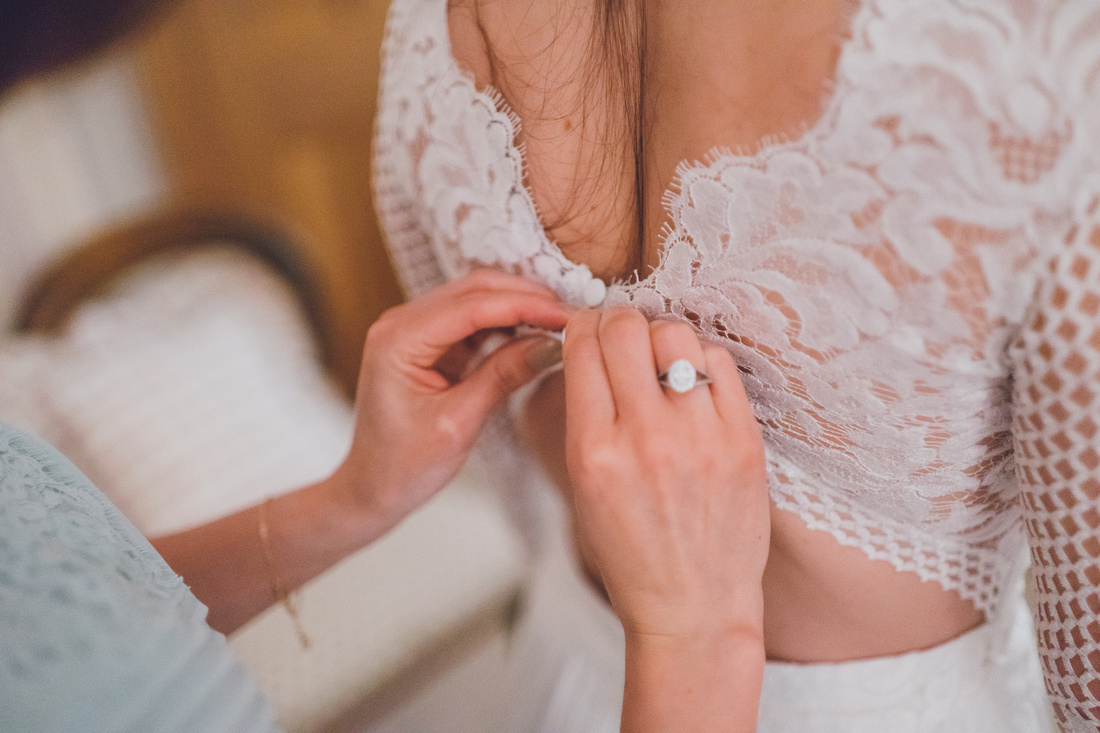 Detail shot of doing up the brides dress