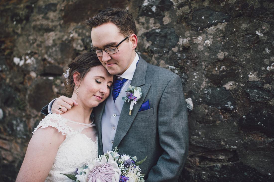 wedding couple cuddling against wall