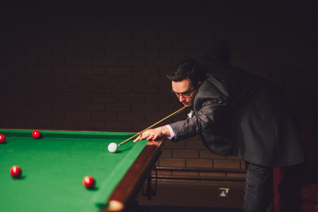 Groom playing snooker