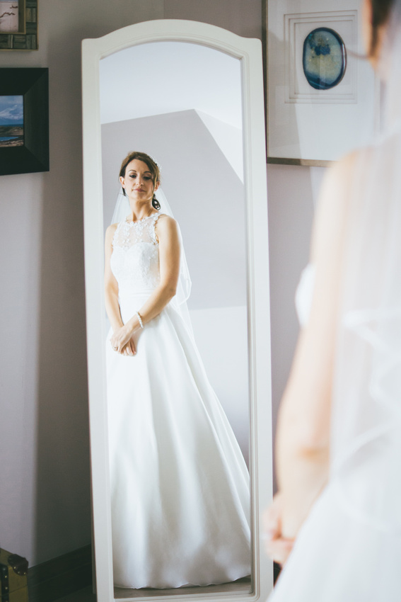 Bride looking into mirror. Waterside hotel bridal prep