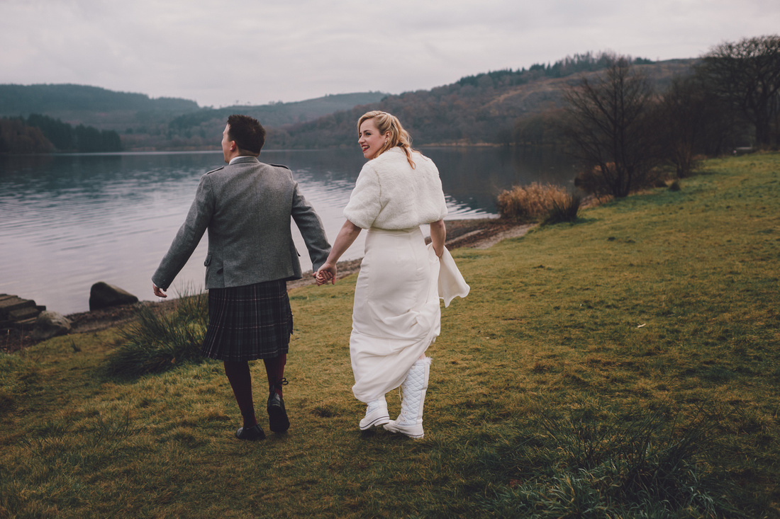 Holding hands Walking white boots Kinlochard Village Hall Wedding Scotland