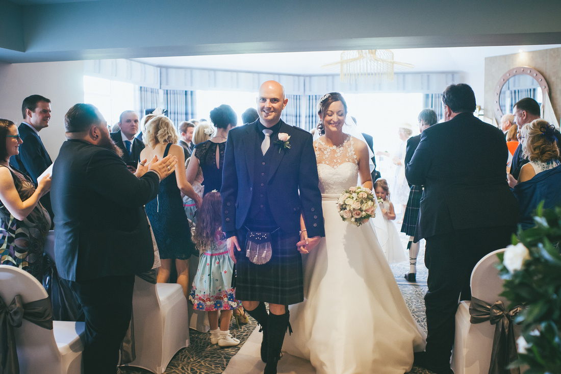 Bride and Groom Walking down the aisle Waterside hotel Ayrshire