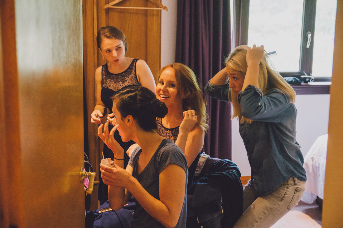 Bridesmaids looking into mirror getting ready