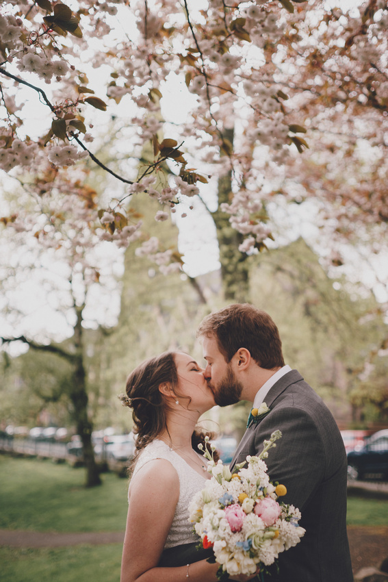 Cottiers Glasgow bride and groom couple kiss in the park with cherry blossom.